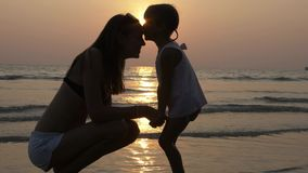 Affectionate feelings of mother and little daughter in silhouette at sunset. Mom and daughter gently conversing at the beach, against the sun in slow motion stock video footage