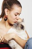 Affectionate Girl. An affectionate young girl puckers up to kiss her Siamese cat stock image