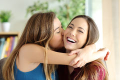 Affectionate girl kissing her sister or friend. Affectionate girl kissing her happy sister or friend in the living room at home with a homey background Stock Photo