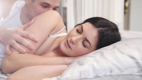 Affectionate guy waking up sleeping girl by kissing and stroking her, young couple wakes up. Family relationships stock footage