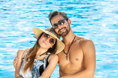 Affectionate happy couple relaxing at a pool. stock photos