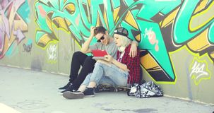 Affectionate hipster urban couple relaxing in town. Sitting on a sidewalk arm in arm looking at a tablet in front of colorful graffiti stock footage