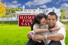 Affectionate Hispanic Couple, New Home and For Sale Real Estate Sign stock photo