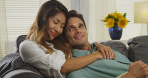Affectionate interracial couple sitting on couch Royalty Free Stock Image