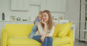 Affectionate daughter comforting her upset mother. Affectionate little daughter embracing sad depressed mother with love and support while sitting on sofa in stock video footage