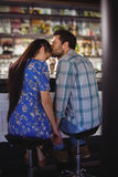 Affectionate man holding hands while kissing woman at counter. In restaurant Stock Photo