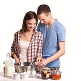 Affectionate man kissing his girlfriend while cutting bread for breakfast in the kitchen stock image