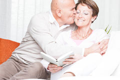 Affectionate man kissing his wife on the cheek Stock Photos