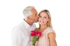 Affectionate man kissing his wife on the cheek with roses Stock Image