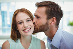 Affectionate man kissing woman. In office Royalty Free Stock Photo