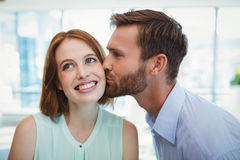 Affectionate man kissing woman. In office Stock Image