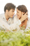 Affectionate man touching woman while looking at her on grass Royalty Free Stock Images