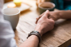 Affectionate man and woman dating in cafe. Close up of male arm holding female hand with gentleness. Couple is drinking coffee while sitting at table Royalty Free Stock Photos