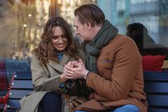 Cute loving couple sitting on bench royalty free stock photos