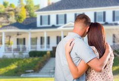 Affectionate Military Couple Looking at Beautiful New House. Affectionate Military Couple Looking at Beautiful New Custom House stock photo