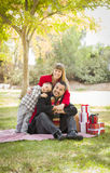 Affectionate Mixed Race Family with Christmas Gifts in the Park Together Stock Photography