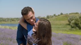 Joyful mixed race couple having fun outdoors. Affectionate mixed race man embracing and tickling adorable laughing woman while enjoying romantic date in floral stock video footage