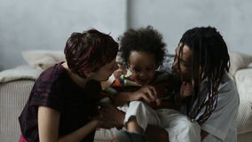 Affectionate mixed race parents kissing little son stock video