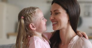 Affectionate mom and child daughter laughing bonding touching noses
