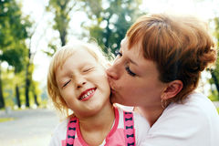 An affectionate mom kissing her little daughter. Royalty Free Stock Images
