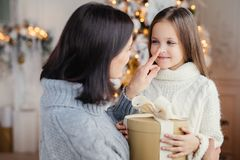 Affectionate mother gives present to her adorble little daughter. Prepares surprise on Christmas, touch her nose, expresses great love. Family, celebration royalty free stock image