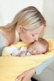 Affectionate mother kissing her baby's forehead Royalty Free Stock Image