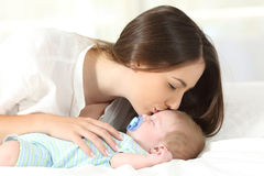 Affectionate mother kissing her baby sleeping. Side view portrait of an affectionate mother kissing her baby sleeping on a bed Royalty Free Stock Photos