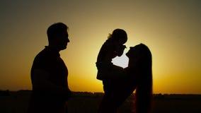 Loving family with child enjoying leisure at sunset