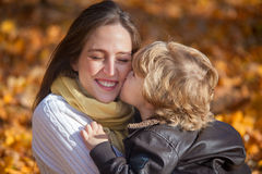 Affectionate mother and son. Loving happy mother embracing her son and enjoying day in nature in autumn. Little boy is kissing his mother on the cheek Stock Photography