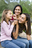 Affectionate mother and two daughters laughing. Affectionate Indian mother and two beautiful mixed-race daughters laughing together Royalty Free Stock Photo