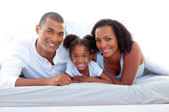 Affectionate parents and their daughter smiling Stock Photos
