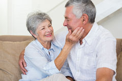 Affectionate retired couple sitting on the sofa Royalty Free Stock Photography