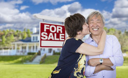 Affectionate Senior Chinese Couple In Front of House and Sign Royalty Free Stock Photos