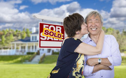 Affectionate Senior Chinese Couple In Front of House and Sign Stock Images