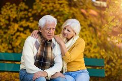 Depressed senior man consoled by elderly woman royalty free stock photography