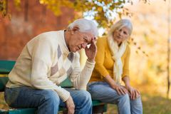 Depressed senior man consoled by elderly woman stock photos