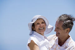 Affectionate senior couple embracing on beach, smiling, side view Stock Photos