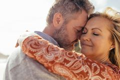 Affectionate senior couple together on beach. Affectionate senior couple embracing outdoors on beach. Beautiful mature women being embraced by her loving husband royalty free stock image