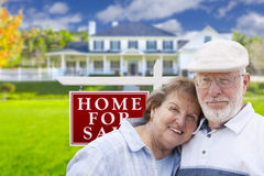 Affectionate Senior Couple Front of For Sale Sign and House Stock Photography