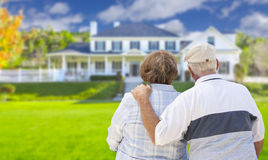Affectionate Senior Couple Looking at Front of House Stock Images