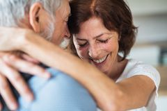 Affectionate senior couple in love standing indoors at home, hugging. An affectionate senior couple in love standing indoors at home, hugging royalty free stock images
