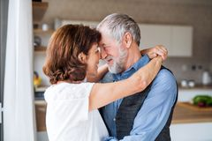 Affectionate senior couple in love standing indoors at home, hugging. An affectionate senior couple in love standing indoors at home, hugging stock images
