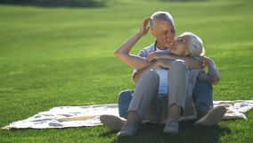 Affectionate senior couple relaxing on green lawn. Affectionate senior attractive couple sitting embraced on green lawn in summer, smiling and laughing while stock footage
