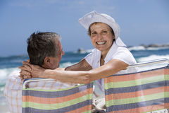 Affectionate senior couple sitting in beach chairs, smiling, rear view, portrait Royalty Free Stock Photography