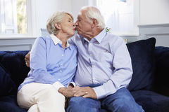 Affectionate Senior Couple Sitting On Sofa At Home stock photos