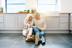 Affectionate senior couple sitting together on their kitchen flo. Affectionate senior couple smiling and looking at each other while sitting together on the stock photos