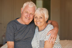 Affectionate senior couple smiliing and hugging in the morning. Portrait of a happy and content senior couple smiling and sitting arm in arm together on their Stock Photos