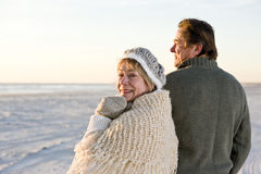 Affectionate senior couple in sweaters on beach Stock Photo