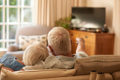 Affectionate senior couple watching television together on their sofa. Rearview of an affectionate senior couple relaxing in each other`s arms and watching Stock Photo
