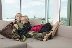 Affectionate siblings in dinosaur and vampire costumes at home Stock Photo